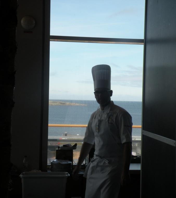 Kock i motljus med havet som kuliss