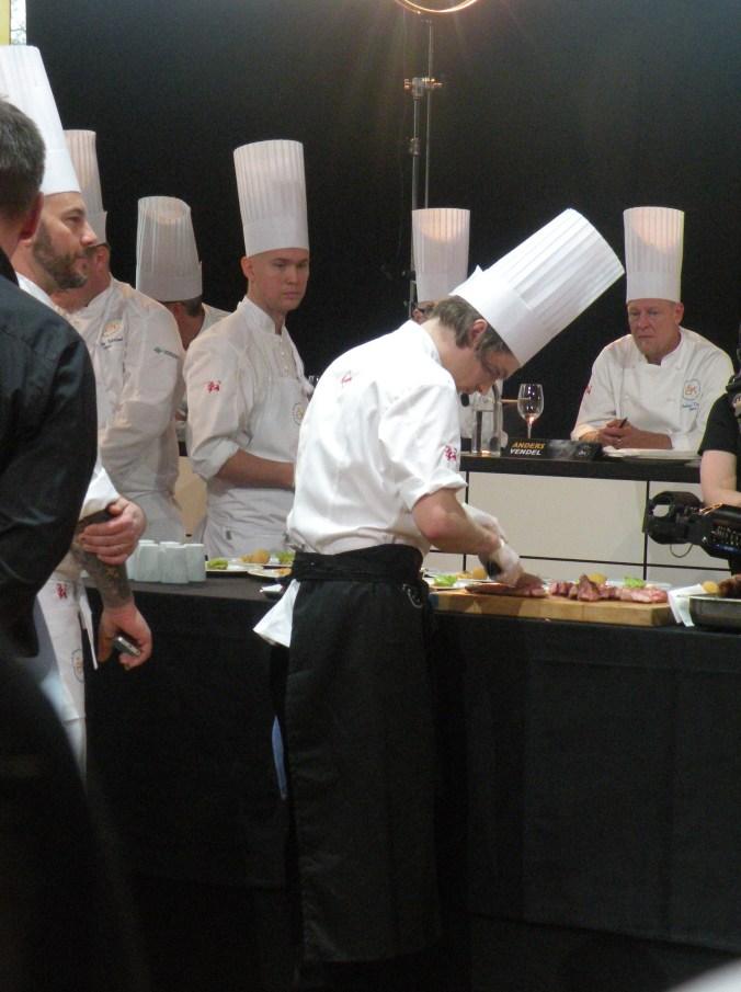 Filip Fastén trancherar anka under juryns överinseende i Årets Kockfinalen 2014