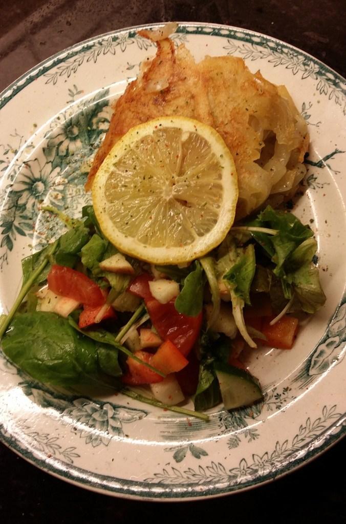 Portion med potatisinbakad fisk och en fräsch sallad.